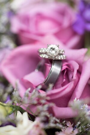 Beautiful wedding rings in lavender rose bouquet Stock Photo
