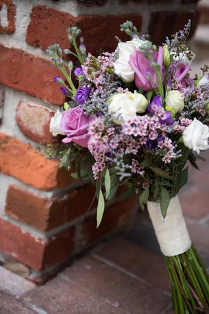Beautiful wedding bouquet leaning against brick
