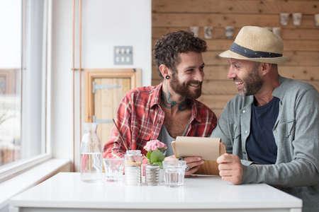同性カップルがカフェで表示メニューを土