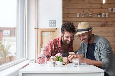同性カップルは土曜カフェ内の携帯電話のコンテンツを共有
