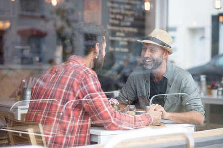 Homosexuell Paar saß den Händen im Kaffee halten