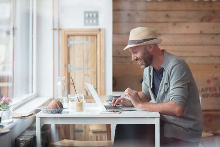 Mid thirties man working on his laptop inside a cafe Stock Photo