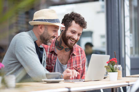 同性カップルに座ってカフェ外共有ノート パソコン