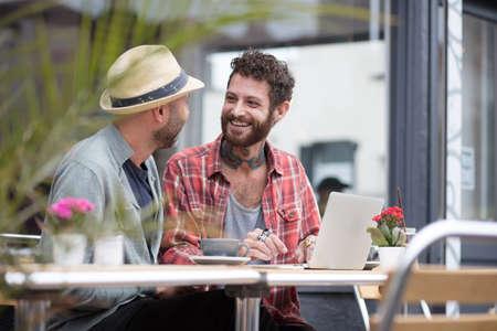 同性カップルに座ってカフェ外共有ノート パソコン 写真素材 - 66851070
