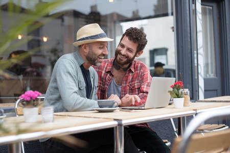 Homosexuell Paar saß Laptop vor einem Café teilen Standard-Bild