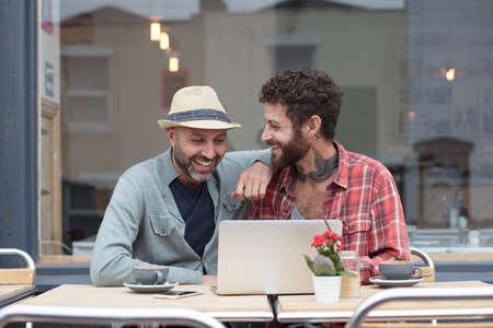 同性カップルに座ってカフェ外共有ノート パソコン 写真素材 - 66852070