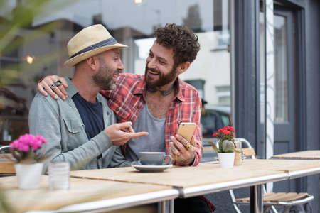 同性カップルは土曜カフェの外で電話のコンテンツを共有 写真素材 - 66852141