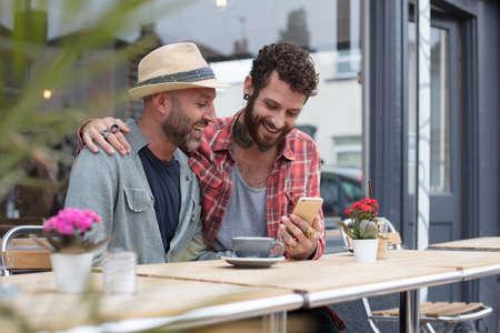 同性カップルは土曜カフェの外で電話のコンテンツを共有 写真素材 - 66851055