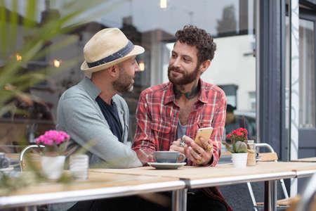 同性カップルは土曜カフェの外で電話のコンテンツを共有