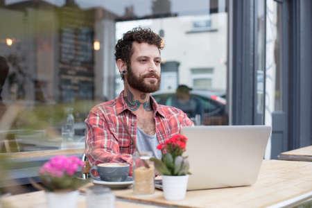 若い入れ墨ヒップスター外のカフェに座って、彼のラップトップを使用して 写真素材