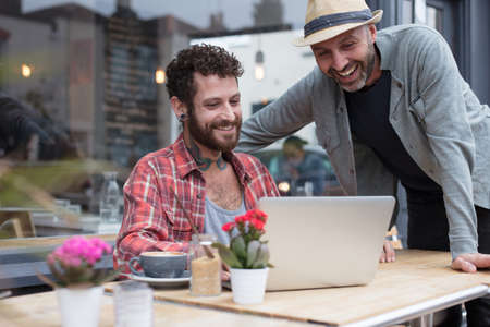 Gay couple sat sharing laptop outside a cafe