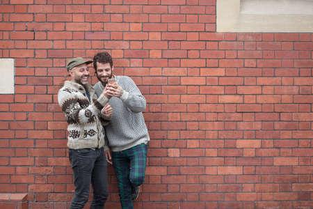 携帯電話のコンテンツを共有、壁を貸して同性カップル 写真素材 - 66852108
