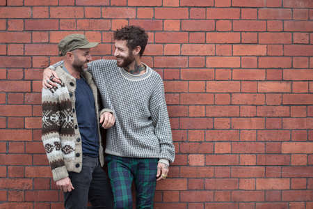 Gay couple lent against a brick wall, laughing Stock Photo