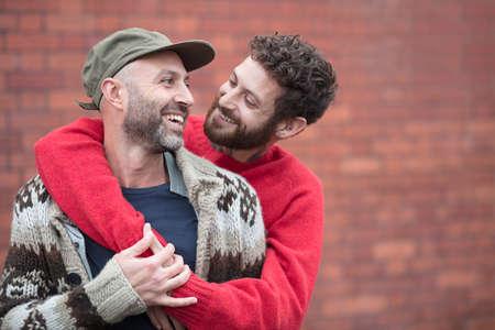 Homosexuelles Paar, das vor Backsteinmauer kuschelt und lacht