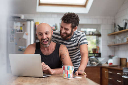 台所でラップトップを使用して同性カップル
