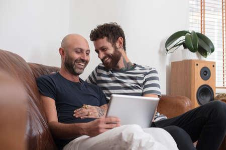 同性カップルは、タブレットを共有ソファに寄り添う土