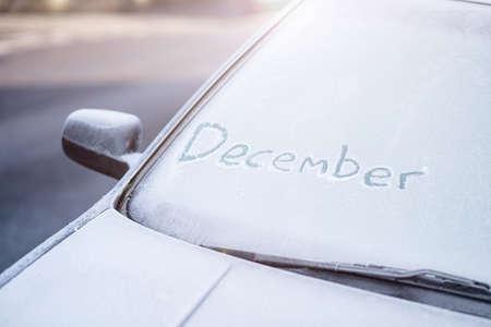 12 月の霜で覆われた車のフロント ガラスに書かれた言葉