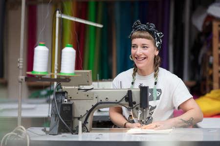 縫製工場環境で若い刺青女性の裁縫師