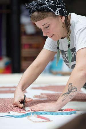 工場環境で切断若い刺青女性の裁縫師 写真素材 - 70499295