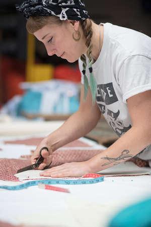 工場環境で切断若い刺青女性の裁縫師 写真素材