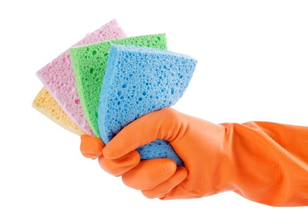 household objects equipment: hand with orange glove holding colorful sponges for cleaning Stock Photo