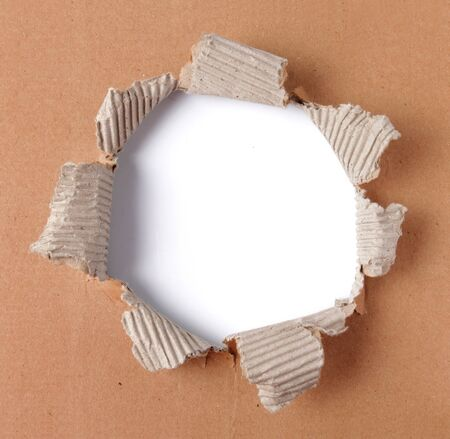 corrugated cardboard: brown corrugated paper torn in the center Stock Photo