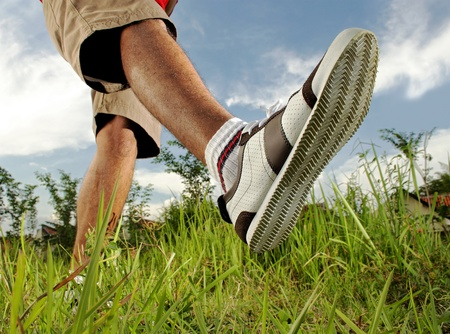 foot step: man walking on the grass Stock Photo