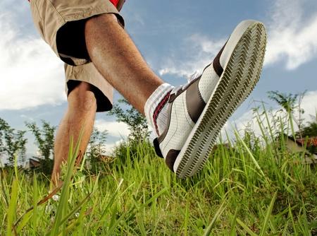 walking shoes: man walking on the grass Stock Photo