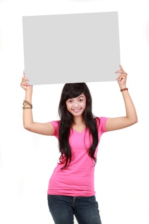 woman holding sign: Portrait of a cute young woman holding a blank board isolated over white background
