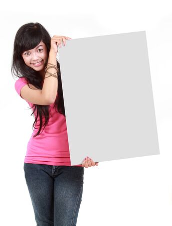 Portrait of an happy young woman holding a blank board against white bacground photo