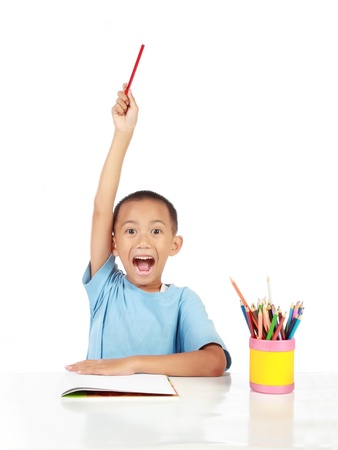 kids writing: confident little schoolboy lift up his hand to answer the question