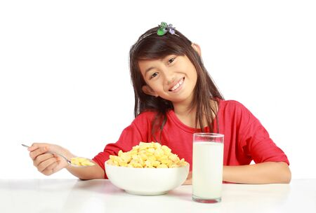 childrens meal: Young girl eating cereal isolated on white background