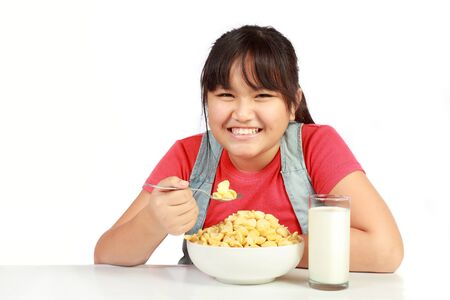hungry kid: portrait of smiling young girl having breakfast against white background
