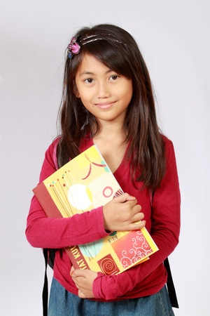 Portrait of girl smiling with backpack and holding books photo