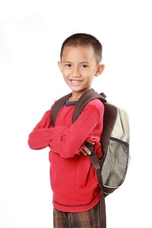 niño con mochila: Retrato de niño con mochila sonriendo sobre fondo blanco Foto de archivo
