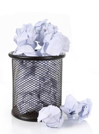 d�bord�: Plein corbeille treillis m�tallique peut avec du papier froiss� dispers�s autour. isol� sur blanc Banque d'images