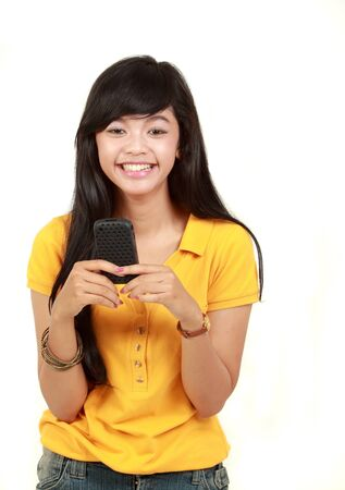 happy young asian girl using her cell phone to send a text message photo