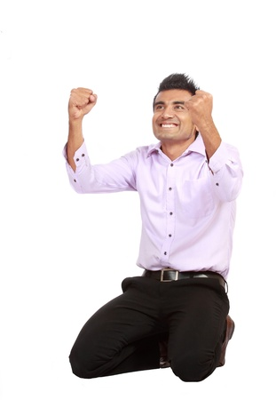 Portrait of an excited young business man celebrating success with good expression against white background