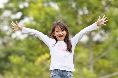 junge Mädchen lächelnd und heben ihre Hände, die Spaß im Freien