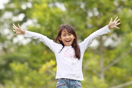 young girl smiling and raise her hands having fun outdoor