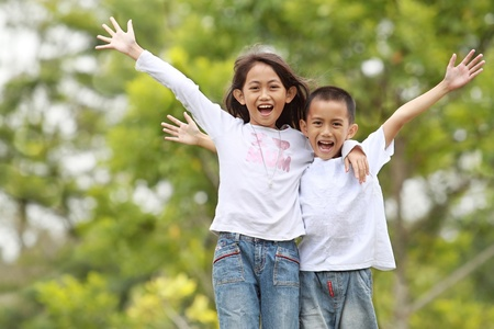 asian school girl: potrait of two kids family outdoor raise their hand and smile Stock Photo