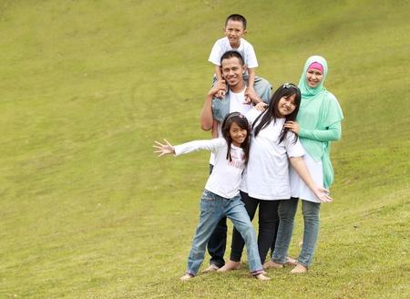 trois enfants: Famille heureuse avec trois enfants. P�re, m�re, filles et fils dans le parc Banque d'images