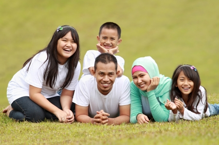 mid twenties: Happy family smiling having a great day in park Stock Photo