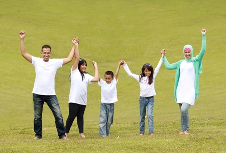 asian family fun: Happy family smiling and raise hand together in the park