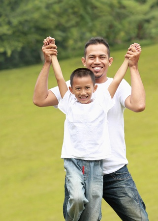 Man and young boy outdoors playing airplane smiling in the park photo