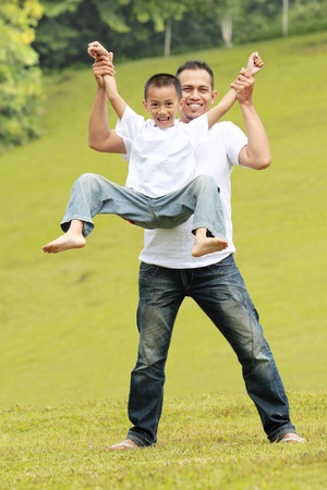 Happy father and son having fun together in the park photo