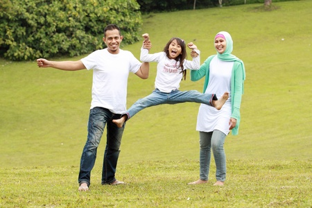 moslem: Portrait of happy parents and their daughter having fun outdoor