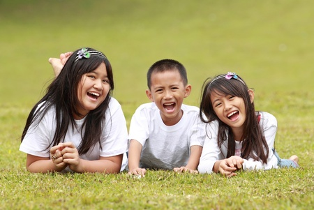 Portrait of happy boy and girls lying on a green grass photo