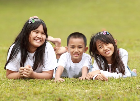 Portrait of happy kids smiling lying on the grass photo