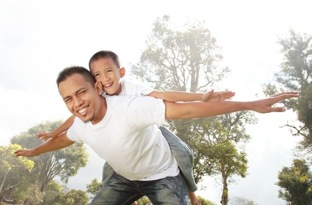 piggyback ride: father giving his son piggyback ride outdoors against sky